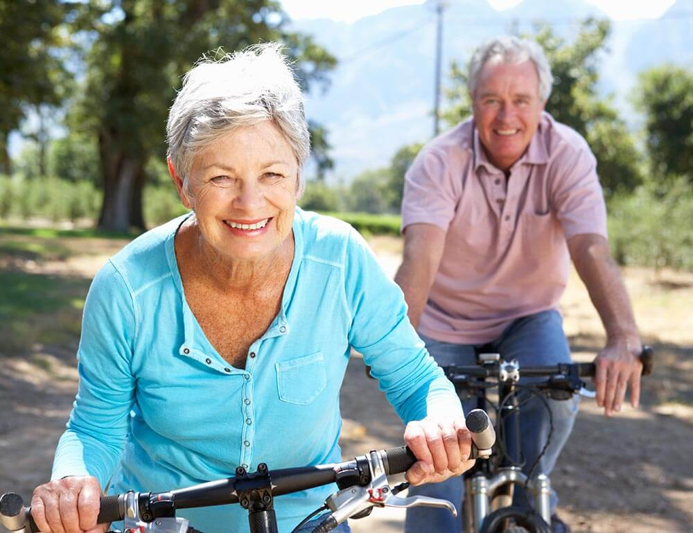 Happy older man and woman riding bike outside