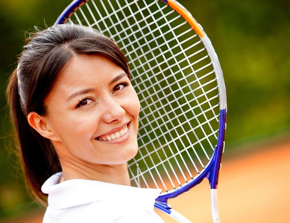 Smiling woman holding a tennis racket