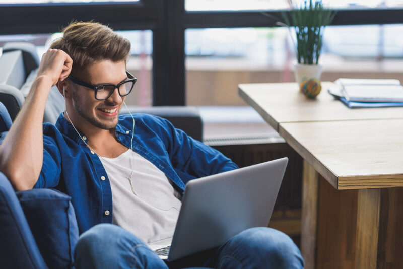 happy man smiling in front of laptop